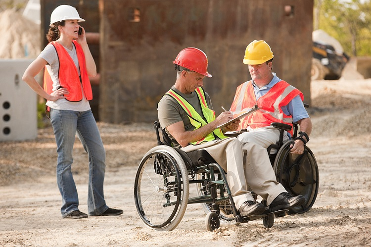 Project engineers in wheelchairs discussing plans on site